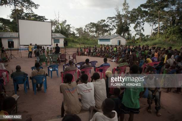 In this photograph taken on October 31 residents of a village of the Mbyaka people gather as they wait for a film screening at a mobile digital...