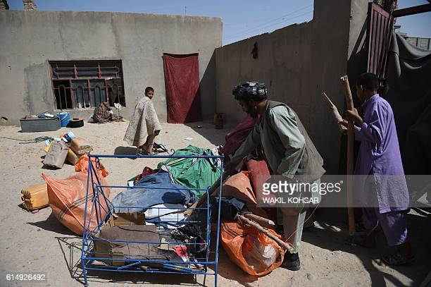 In this photograph taken on October 4 an internally displaced Afghan family unload their belongings after arriving from Nad-Ali district to Lashkar...