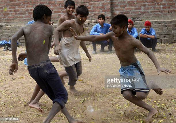 In this photograph taken on October 5 Indian schoolchildren play Kabaddi at their government school in the village of Sarai Amanat Khan near the...