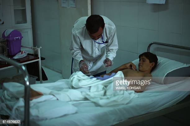 In this photograph taken on October 6 a wounded Afghan boy receives medical treatment at Emergency hospital in Lashkar Gah the capital city of...