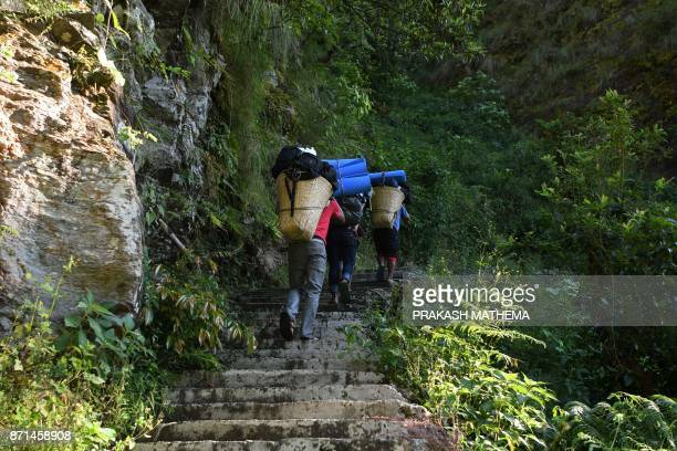 In this photograph taken on October 7 Nepali people carry goods along a restored trail in Dhading some 100km northwest of Kathmandu Lapa a village in...