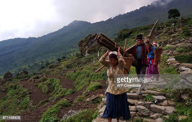 In this photograph taken on October 7 Nepali people walk along restored trails in Dhading some 100km northwest of Kathmandu Lapa a village in Dhading...