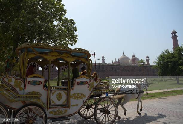 In this photograph taken on October 7 tourists ride on a horse buggy as they look at the historic Badshahi Mosque in Lahore Lahore which once served...