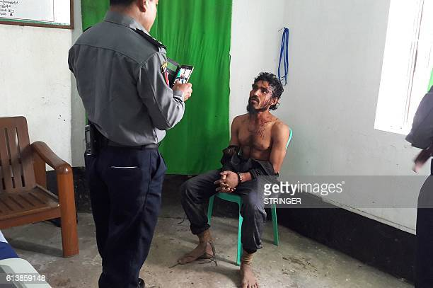 In this photograph taken on October 9 a man suspected of being one of the attackers in recent border raids is taken to a police station in Sittwe...