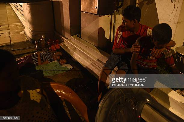 In this photograph taken on on May 18 Sri Lankan flood victims rest by a road camp in Kelaniya suburb of the capital Colombo Rescue workers on May 18...