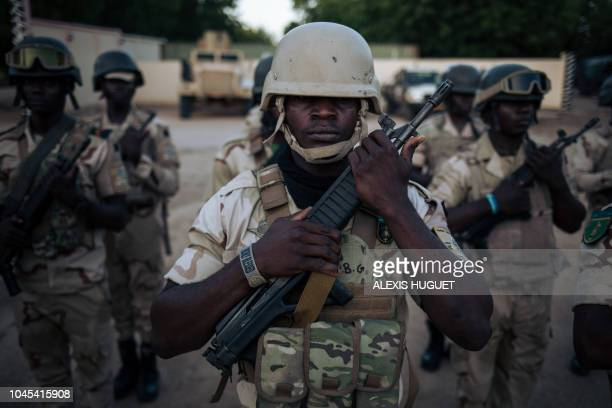 TOPSHOT In this photograph taken on on September 28 soldiers conduct the daily flaglowering ceremony at the Force Multinationale Mixte Sector No 1...