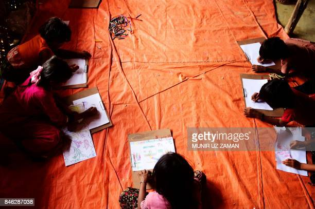 TOPSHOT In this photograph taken on September 11 Rohingya Muslim refugee children draw pictures at a safe house in Kutupalong refugee camp in the...