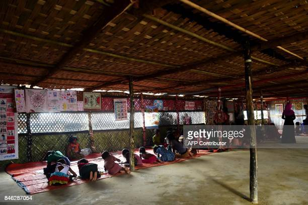 In this photograph taken on September 11 Rohingya Muslim refugee children draw pictures at a safe house in Kutupalong refugee camp in the Bangladeshi...