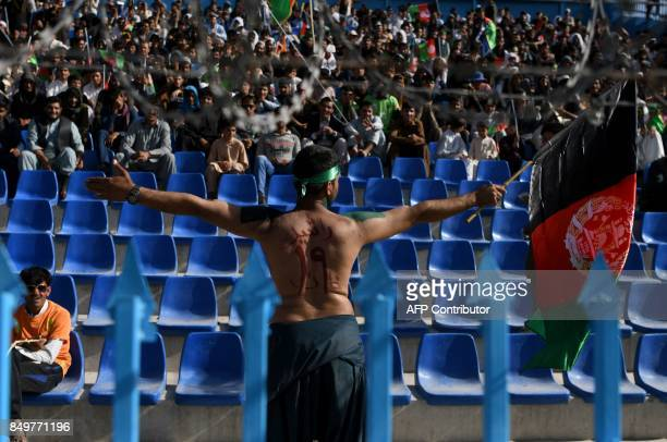 In this photograph taken on September 18 2017 an Afghan cricket fan waves the Afghan national flag as his back has the name of Afghan national team...