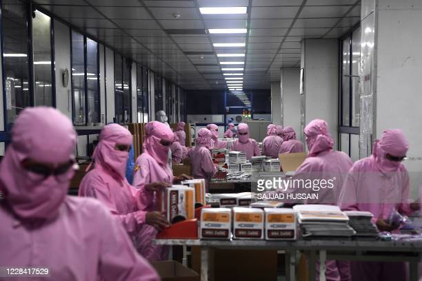In this photograph taken on September 2 workers pack syringes at the Hindustan Syringes factory in Faridabad. - India's biggest syringe manufacturer...