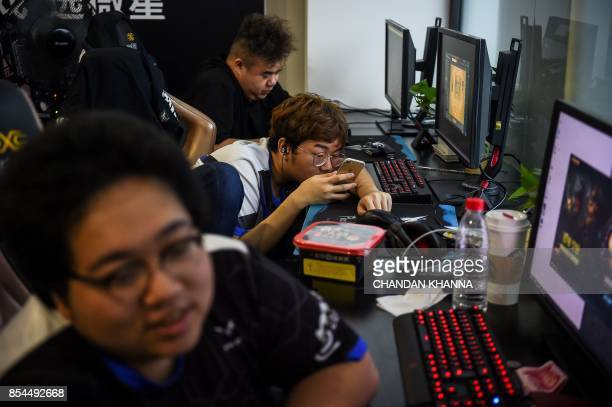In this photograph taken on September 20 a Taiwanese gamer from the eSports team Flash Wolves looks at his phone during training for the League of...