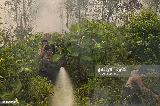 In this photograph taken on September 24 Indonesian policemen extinguish a fire on a vast area of burning peat land forest in the Kapuas district in...