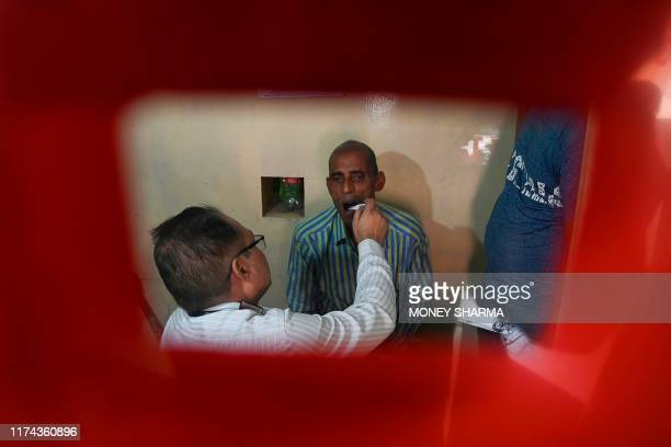 In this photograph taken on September 26 a doctor checks a suspected tuberculosis patient at a DOTS Centre in New Delhi All the symptoms were there...