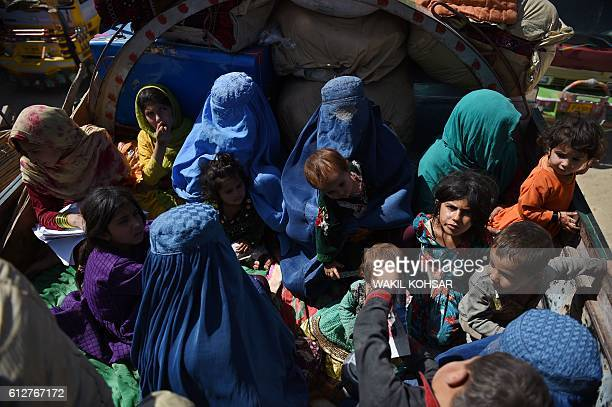 In this photograph taken on September 27 Afghan refugee families sit in a truck as they return to Afghanistan from the Pakistan border, at the United...