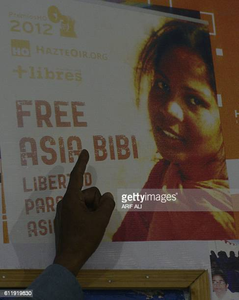 In this photograph taken on September 27 Ashiq Masih husband of Asia Bibi a Christian woman facing death sentence for blasphemy points to a poster...