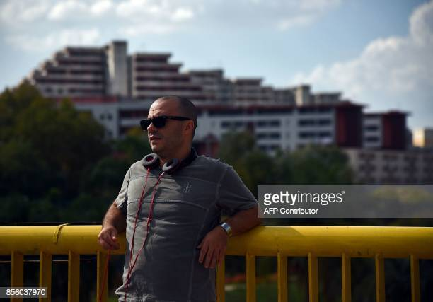 In this photograph taken on September 27 tour guide Daniele Sanzone poses in front of the building 'Le Vele' in Scampia on the outskirts of Naples...