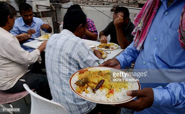 In this photograph taken on September 29 Indian workers from the eastern state of Bihar eat lunch on the terrace of a hotel in New Delhi, after they...