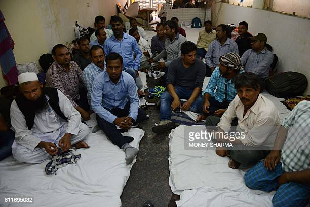 In this photograph taken on September 29 Indian workers from the eastern state of Bihar gather in a hotel in New Delhi, after they were repatriated...