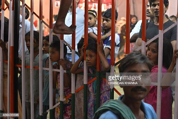 In this photograph taken on September 30 Indian children peer through a barrier to watch a magic show at a fair to celebrate the Dusshera festival in...