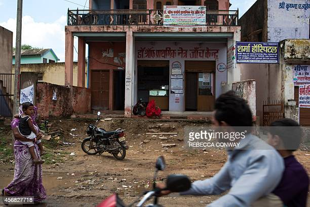 In this photograph taken on September 4 Indian residents wait outside as the Dr Shroff Charity Eye Hospital Vision Centre opens in Thanagazi some 47...