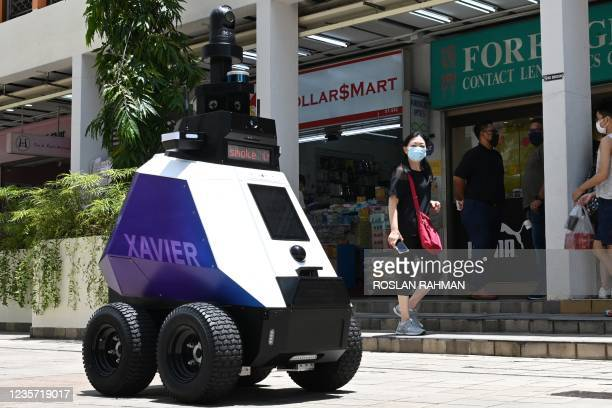 """In this photograph taken on September 6 an autonomous robot named """"Xavier"""" patrols a shopping and residential district during a three-week trial by..."""