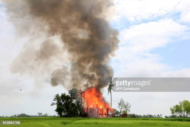 TOPSHOT In this photograph taken on September 7 a house burns in Gawdu Tharya village near Maungdaw in Rakhine state in northern Myanmar The wooden...