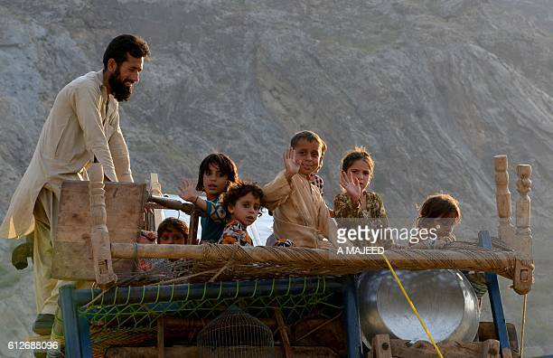 In this photograph taken on September 7 a repatriated Afghan refugee family travel on a loaded vehicle as they prepare to cross the border into...