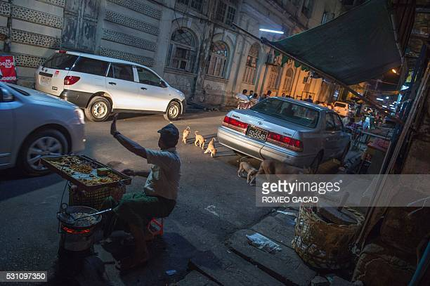 In this photograph taken on the night of May 12 a vendor stops a car while a dog with four puppies cross the street in Yangon / AFP / ROMEO GACAD