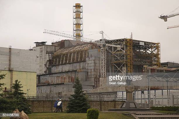 In this photograph taken through a bus window workers walk near the sarcophagus that encloses stricken reactor number four at the Chernobyl nuclear...