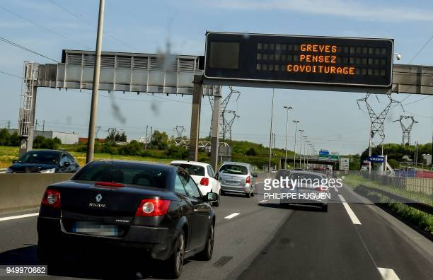 In this photograph taken through a car windscreen vehicles pass under an information board which reads as 'strikes think carpooling' on a highway...