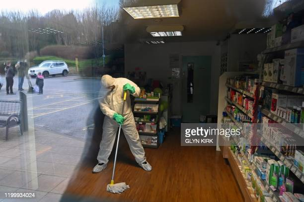 In this photograph taken through a window, a worker in protective clothing, including face mask and gloves, is pictured cleaning the floor of the...