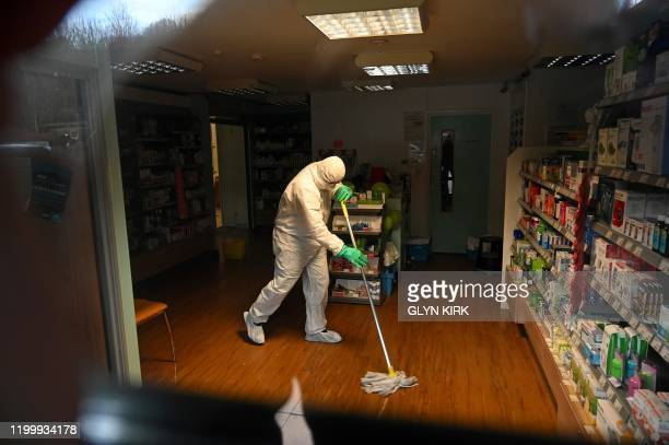 In this photograph taken through a window a worker in protective clothing including face mask and gloves is pictured cleaning the floor of the...