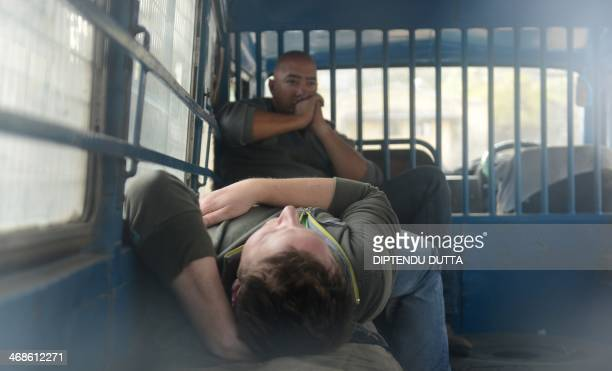 In this photograph taken through a window mmbers of a foreign television crew wait inside a police vehicle transporting them to a court hearing at...