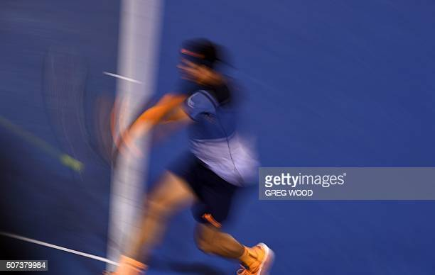In this photograph taken with a slow shutter speed Canada's Milos Raonic plays a backhand return during his men's singles semifinal match against...