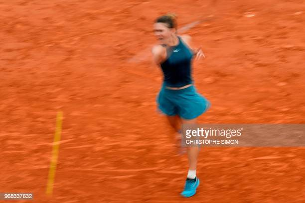 In this photograph taken with a slow shutter speed Romania's Simona Halep plays a forehand return to Germany's Angelique Kerber during their women's...