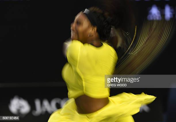 TOPSHOT In this photograph taken with a slow shutter speed Serena Williams of the US plays a forehand return during her women's singles match against...