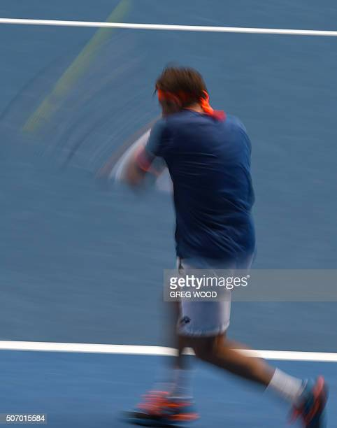 In this photograph taken with a slow shutter speed Spain's David Ferrer plays a backhand return during his men's singles match against Britain's Andy...
