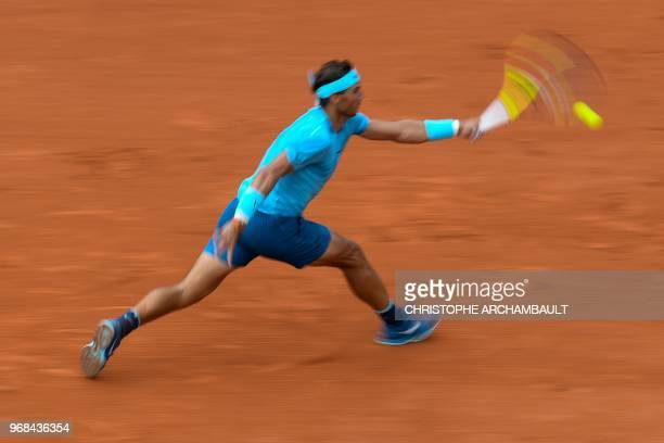 In this photograph taken with a slow shutter speed Spain's Rafael Nadal returns the ball to Argentina's Diego Schwartzman during their men's singles...