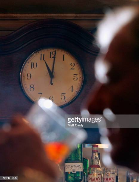 In this photo-illustration A man drinks, as the pub clock passes 11pm signalling 'time at the bar', in a traditional public house, the Star Inn on...