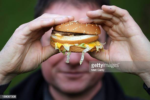 In this photoillustration a man holds a burger purchased from a fast food outlet on January 7 2013 in Bristol England A governmentbacked TV advert...