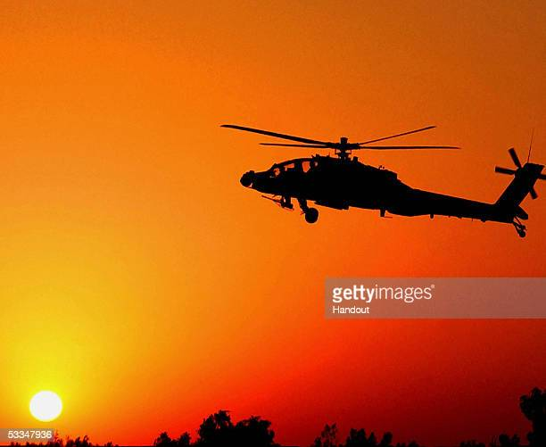In this picture released by US Army on August 2005 a US Army A64 Apache helicopter prepares to land as the sun comes up on July 23 2005 at Camp Taji...