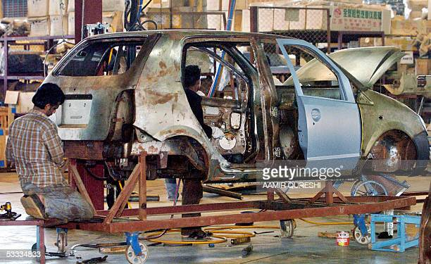 WITH PAKISTANECONOMYAUTO In this picture taken 02 July 2005 Pakistani technicians work on the first Pakistani car Revo at its assembling plant in Bin...