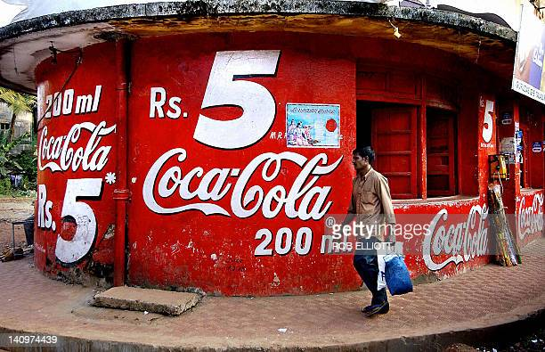 In this picture taken 03 December 2003 An Indian man walks past the bottom section of a three storey corner store emblazoned with CocaCola signage...