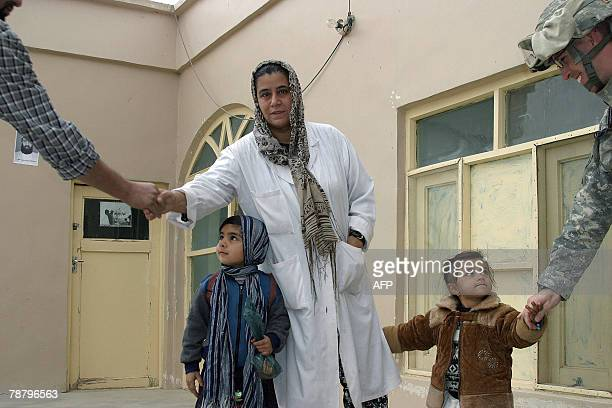 In this picture taken 03 January 2008 The only Afghan woman doctor at the hospital Arefa Shekiba shakes hands with visitors from the International...