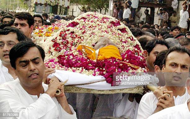 In this picture taken 07 July 2002 Mukesh and Anil Ambani carry the body of their father Dhirubhai Ambani founder and chairman of India's largest...