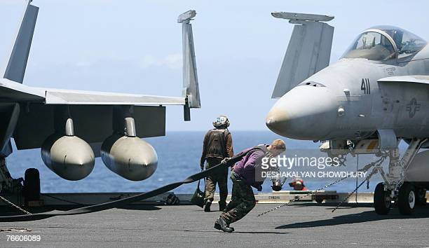 In this picture taken 07 September 2007, a US Navy crewman pulls a fuelpipe across the deck of USS Kitty Hawk aircraft carrier in the Bay of Bengal,...