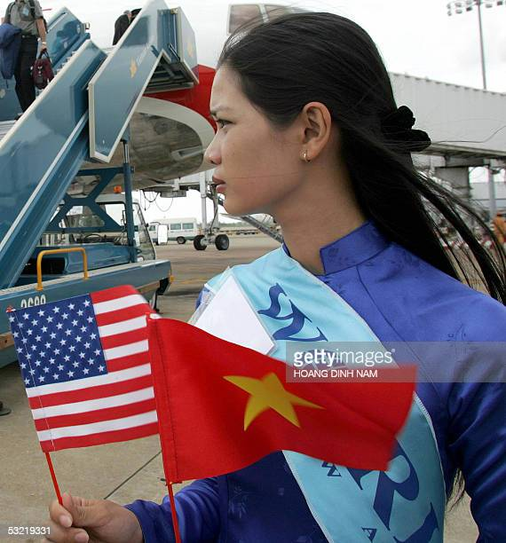 In this picture taken 15 June 2005 a Vietnamese girl wearing a traditional 'ao dai' dress holds Vietnamese and US flags to welcome American guests at...