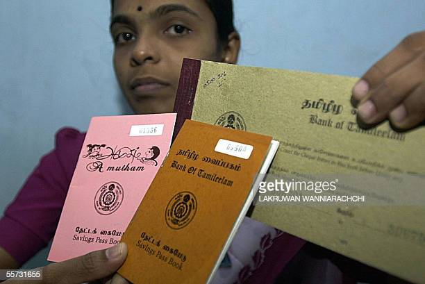 In this picture taken 16 September 2005 an employee of the Sri Lankan Bank of Tamileelam displays a selection of pass and cheque books at the banks'...