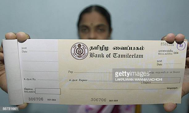 BANK In this picture taken 16 September 2005 an employee of the Sri Lankan Bank of Tamileelam displays a cheque book at the banks' branch in...