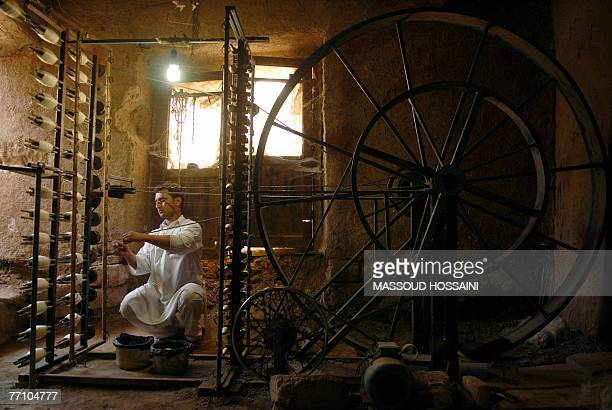 In this picture taken 16 September 2007 an Afgan man works on silk threads at a Silk industry factory in Herat west of Kabul In Herat once an...